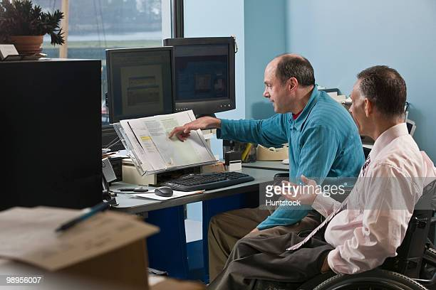 two businessmen in an office, one with friedreich's ataxia and another with spinal cord injury - assistive technology stock photos and pictures