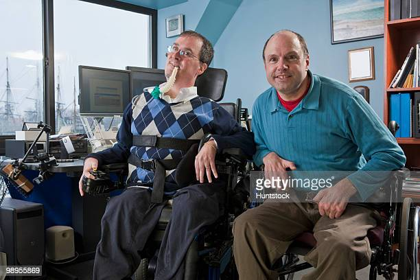 two businessmen in an office, one with muscular dystrophy and breathing ventilator and another with friedreich's ataxia - duchenne muscular dystrophy stock photos and pictures