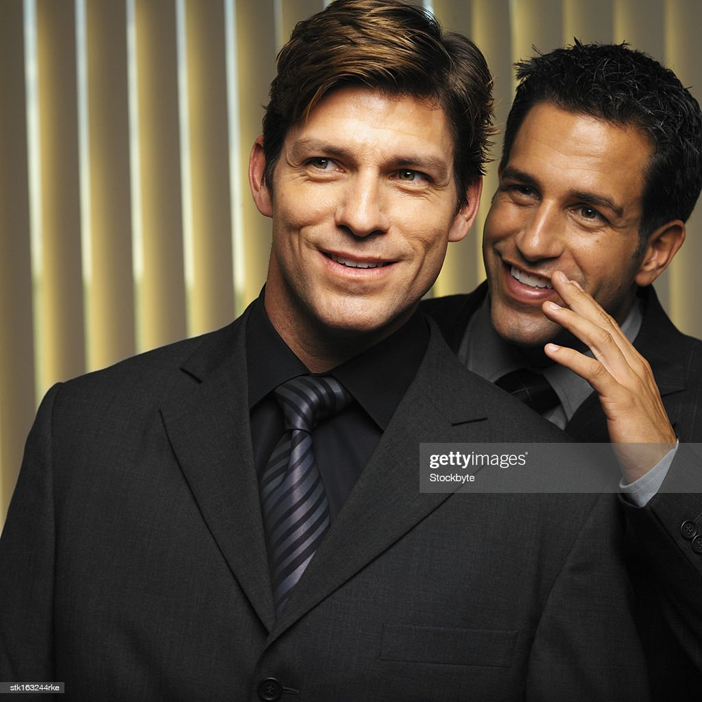 two businessmen in black suits whispering portrait : Stock Photo