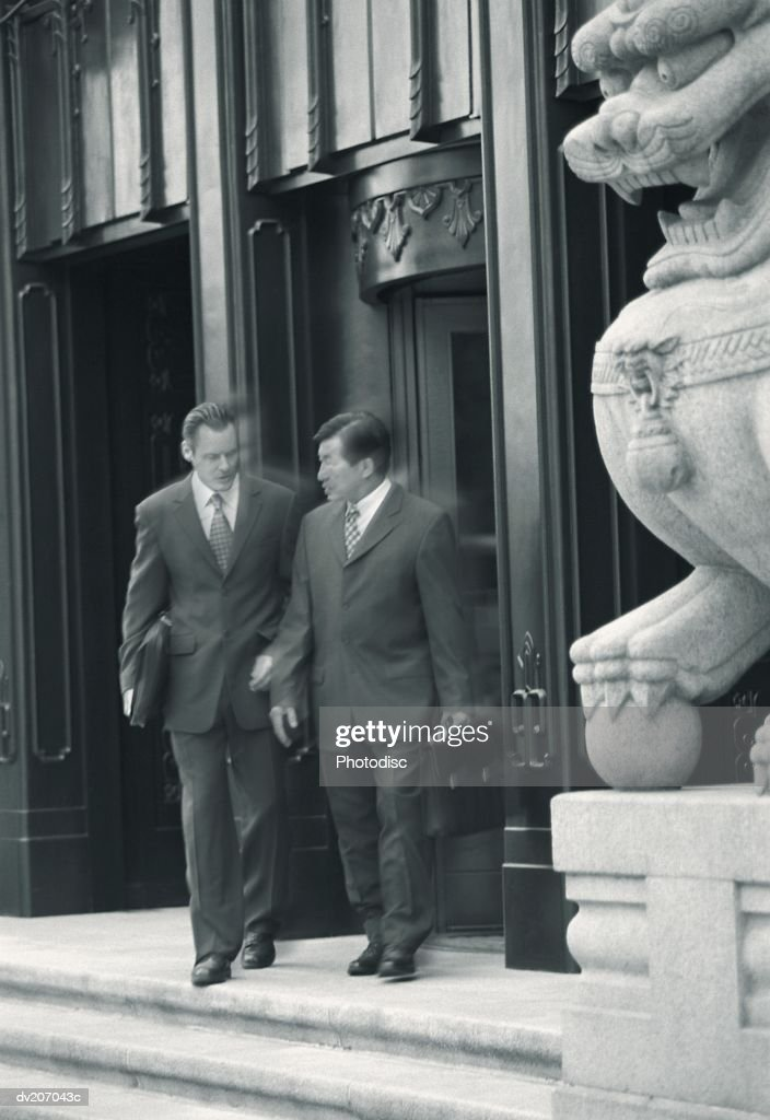 Two businessmen in building entryway : Stock Photo