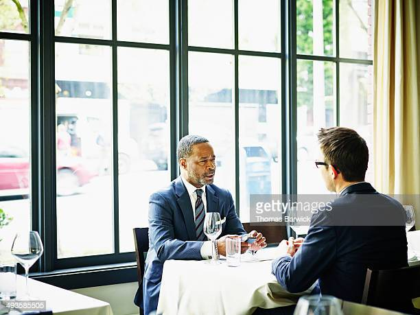 Two businessmen in discussion at business lunch