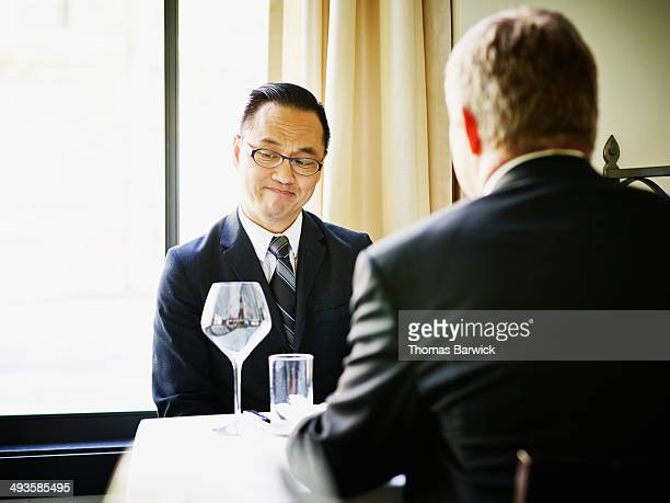 Two businessmen in discussion at lunch meeting