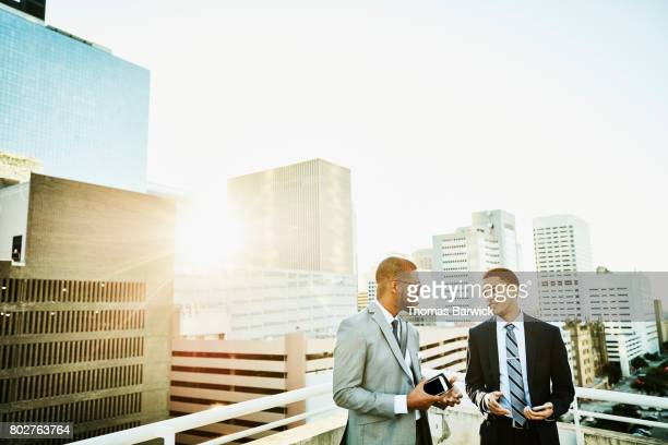 Two businessmen in discussion on downtown office deck