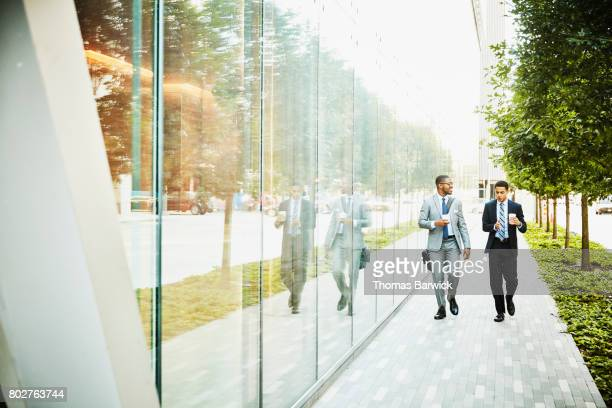 Two businessmen in discussion walking on city sidewalk