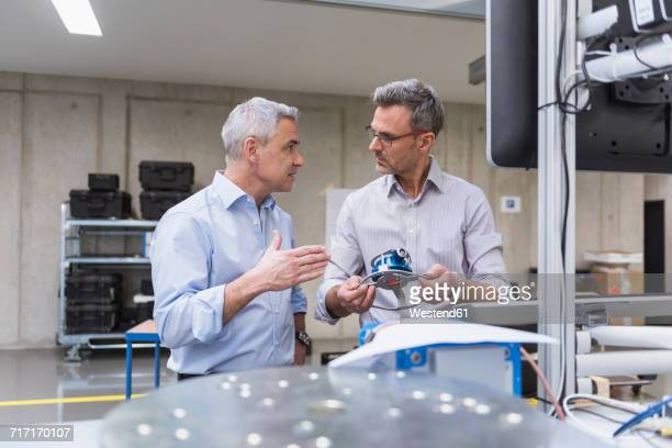 two businessmen in factory hall examining product - finanzen und wirtschaft stock-fotos und bilder