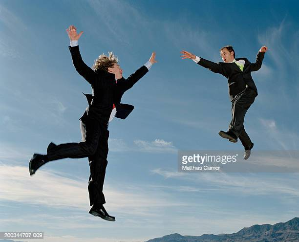Two businessmen in mid-air reaching out to each other, side view