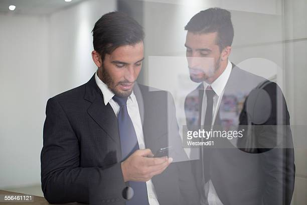 Two businessmen in office looking at cell phone