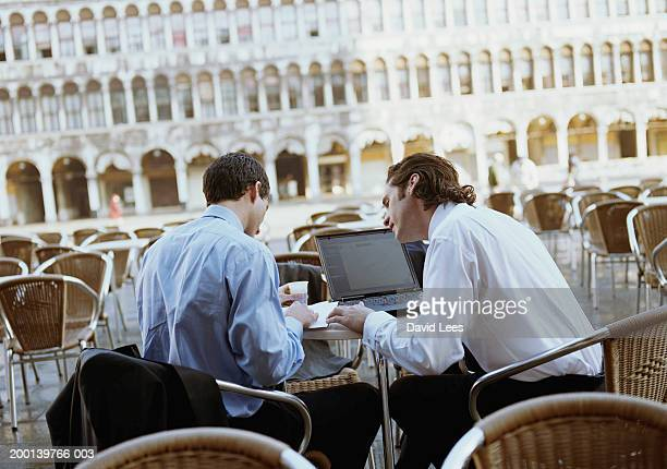 Two businessmen in outdoor cafe with laptop, rear view