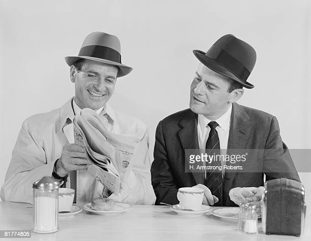 Two businessmen in suits and fedoras having breakfast at diner, looking at newspaper.