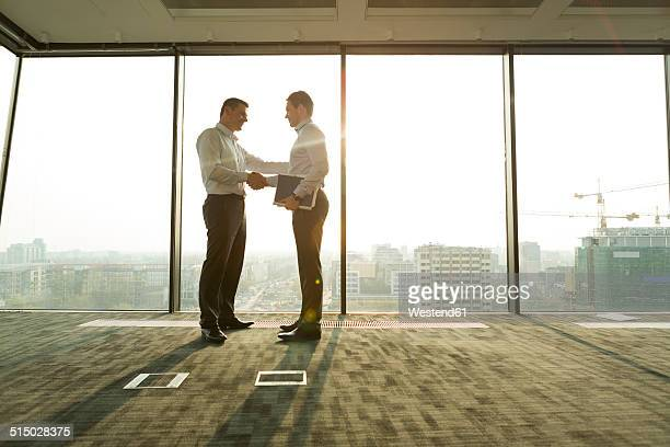 two businessmen in sunny office shaking hands - 商業不動産 ストックフォトと画像