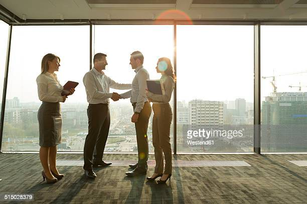 two businessmen in sunny office shaking hands - truth be told stock photos and pictures