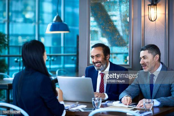two businessmen interviewing female candidate in cafe with laptop - financial occupation stock pictures, royalty-free photos & images