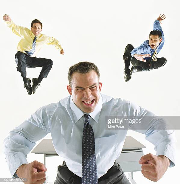 Two businessmen jumping in air, one man flexing muscles in foreground