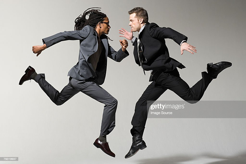 Two businessmen jumping : Stock Photo