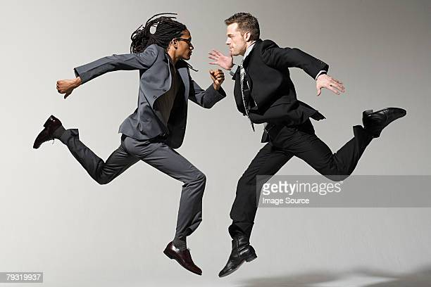 two businessmen jumping - black suit stock pictures, royalty-free photos & images