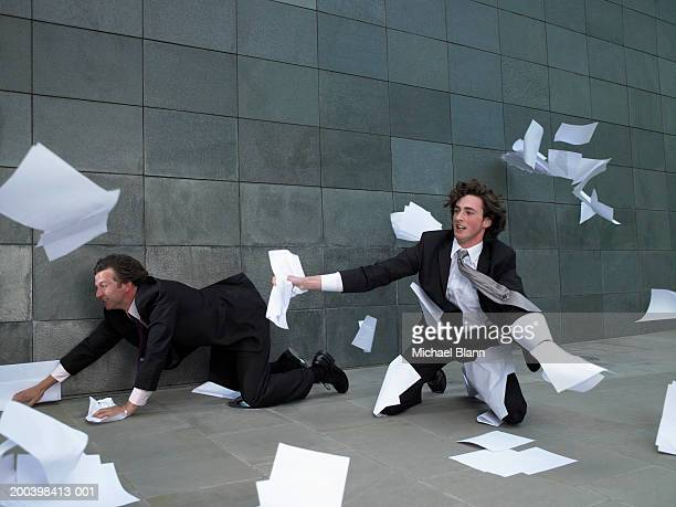 Two businessmen kneeling on pavement, grabbing paper blowing in wind