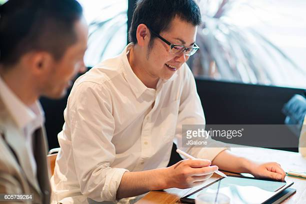 Two businessmen looking at a digital tablet