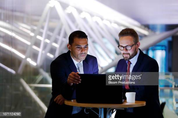 two businessmen looking at a laptop in waiting area - financial occupation stock pictures, royalty-free photos & images