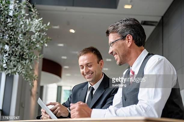 Two businessmen looking at digital tablet