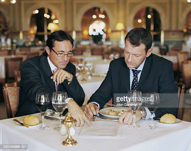 Two businessmen looking at document at restaurant table, one pointing