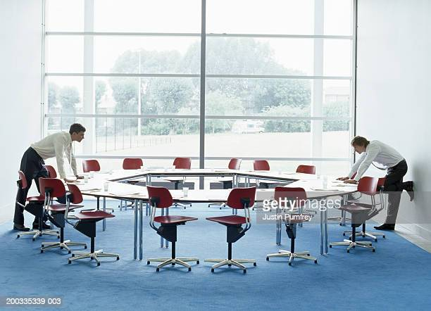 Two businessmen looking at each other over round table in meeting room