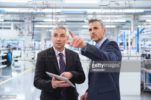 Two businessmen looking at graphic on glass pane in factory hall