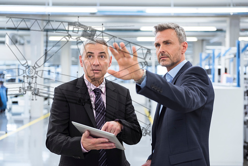 Two businessmen looking at graphic on glass pane in factory hall - gettyimageskorea