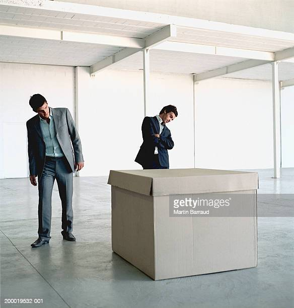 Two businessmen looking at large cardboard box