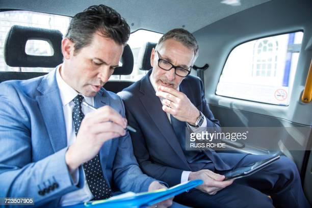 Two businessmen looking at paperwork in taxi cab