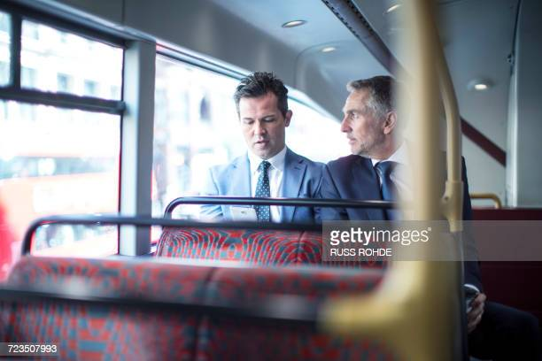 Two businessmen looking at smartphone on double decker bus