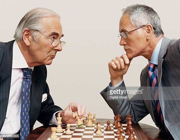two businessmen looking face to face and playing chess - 勝負 ストックフォトと画像