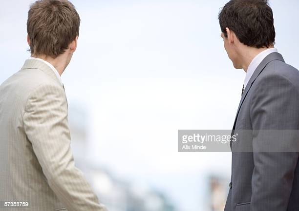 Two businessmen looking into the distance, rear view