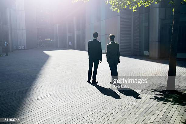 Two businessmen looking into the sun.