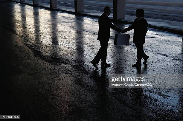 Two businessmen meeting in a parking lot