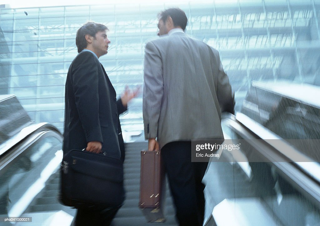 Two businessmen on escalators, low angle view : Stockfoto