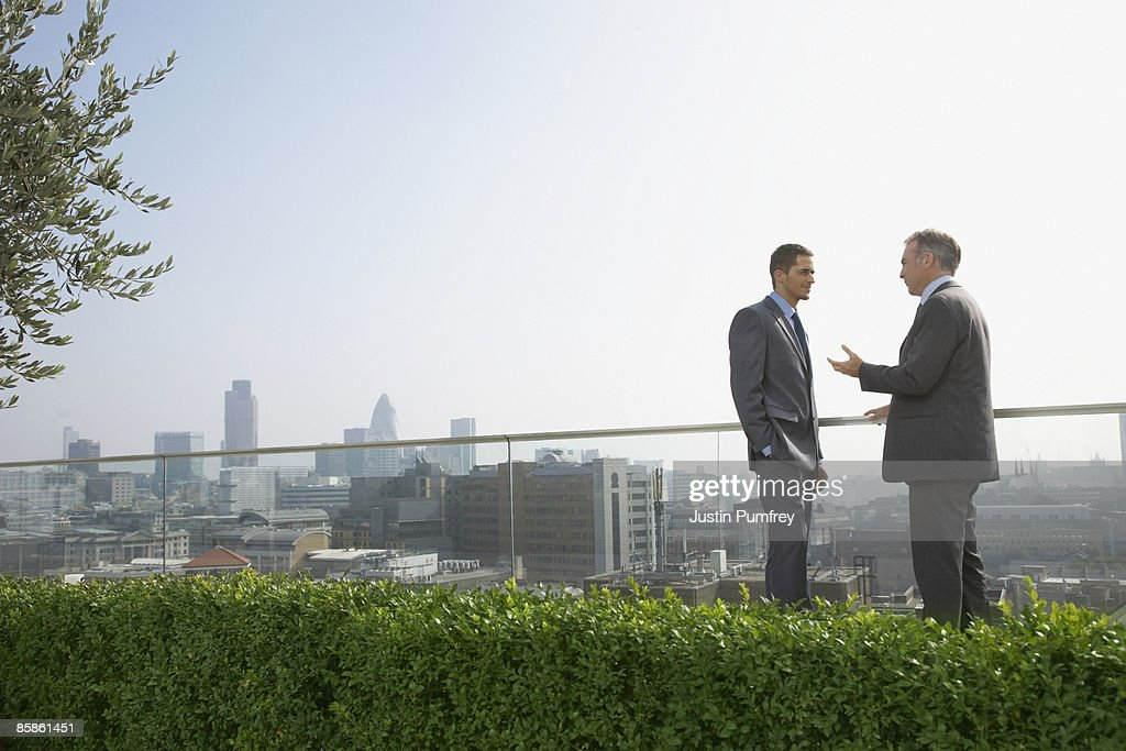 Two businessmen on rooftop talking, side view  : Stock-Foto