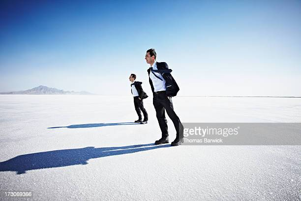 Two businessmen on salt flats leaning into wind