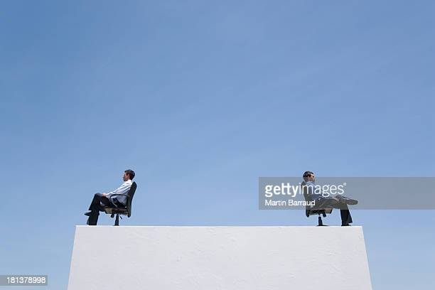 Two businessmen on wall with office chairs