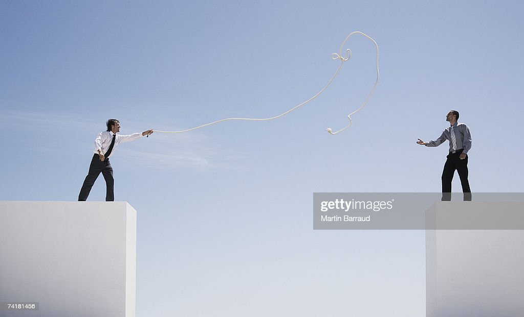 Two businessmen on walls outdoors with gap and rope : Stock Photo