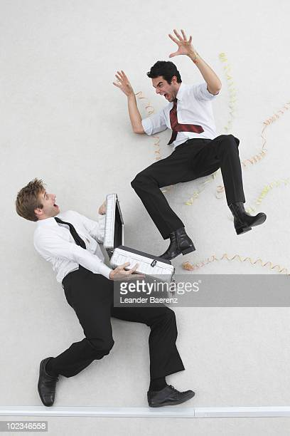 Two businessmen, one holding briefcase, the other scaring him, elevated view