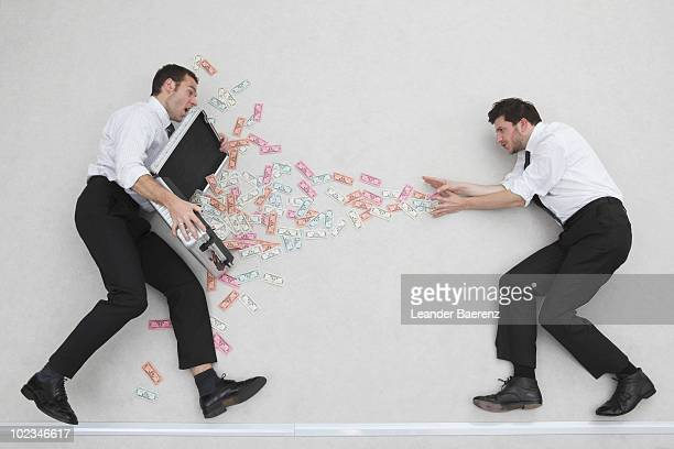 Businessman pulling money from case, side view, portrait, elevated view