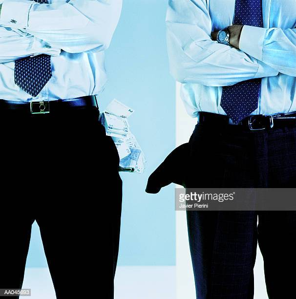 Two businessmen, one with pocket full of money