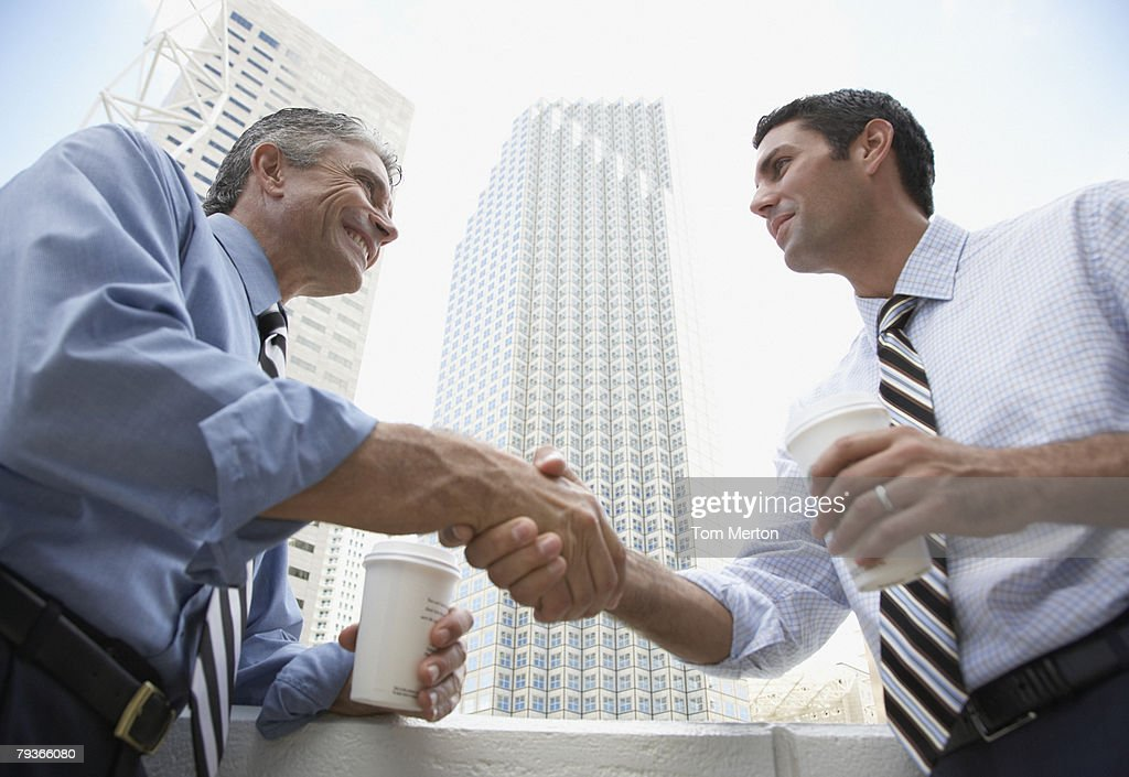 Two businessmen outdoors on a balcony shaking hands holding coffee cups : Stock Photo