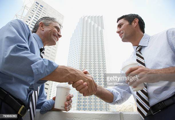 Two businessmen outdoors on a balcony shaking hands holding coffee cups