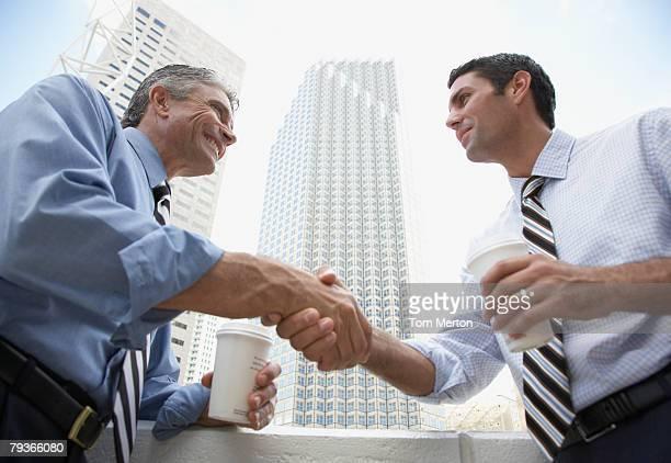 Zwei Geschäftsleute im Freien auf einem Balkon, schütteln Hände holding Coffee