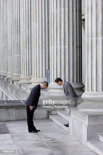 Two businessmen outdoors on steps bowing