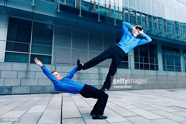 two businessmen performing an acrobatic stunt together - acrobatic activity stock photos and pictures