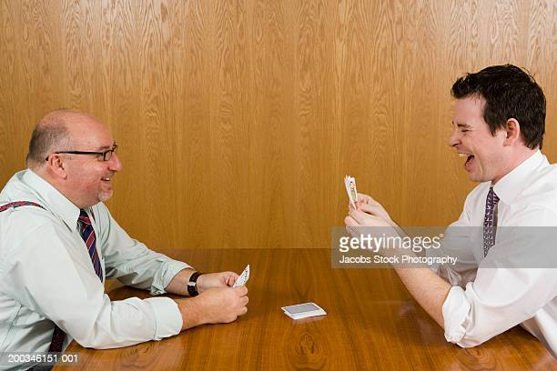Two businessmen playing cards on boardroom table, smiling, side view