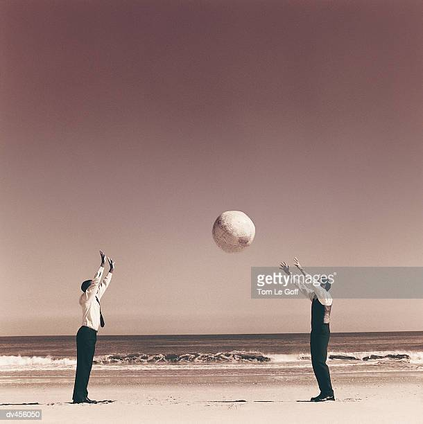 Two businessmen playing catch with globe