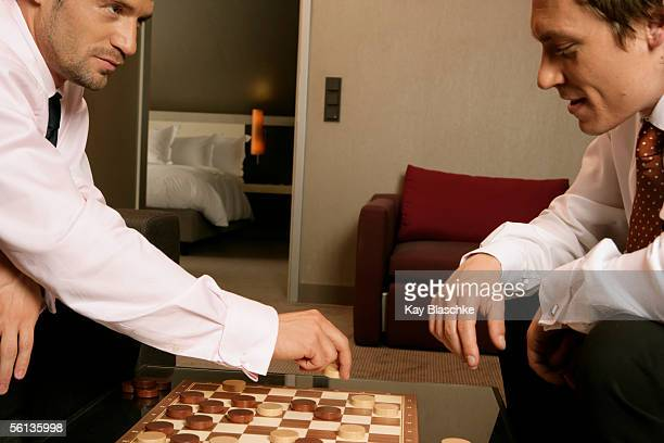Two businessmen playing checkers